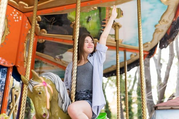 カルーセルで楽しんでいるスマイリー女性 無料写真