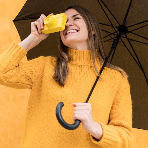 Улыбающаяся женщина с черным зонтом и желтой камерой Бесплатные Фотографии