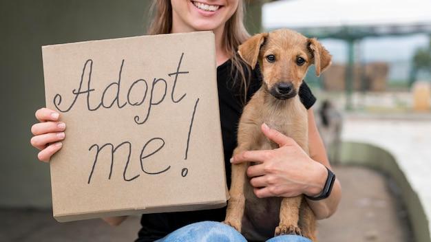 Смайлик женщина, держащая усыновить меня знак и спасательная собака Бесплатные Фотографии