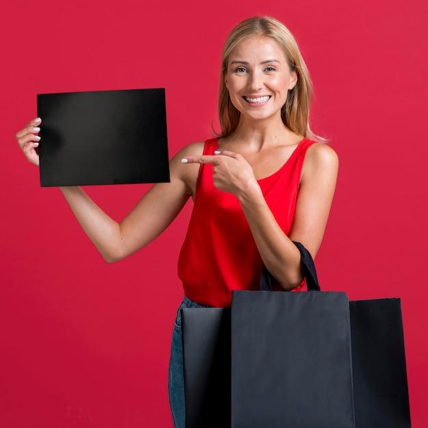 Смайлик женщина держит пустой знак и много сумок Бесплатные Фотографии