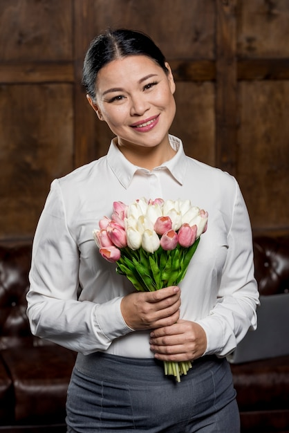 Smiley woman holding bouquet of flowers Free Photo
