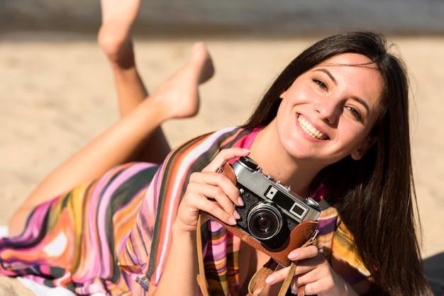 Fotocamera sorridente della holding della donna mentre sedendosi sulla sabbia della spiaggia Foto Gratuite