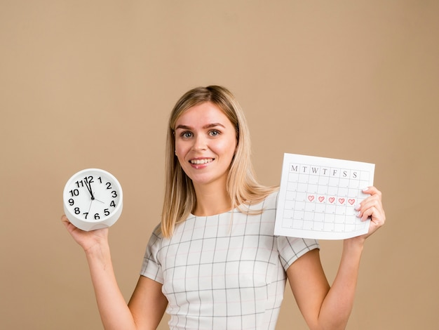 Smiley woman holding a clock and her period calendar Free Photo