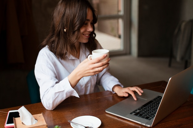 Smiley woman holding cup of coffee and working on laptop Free Photo