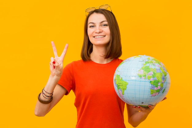 Smiley woman holding globe and making peace sign Free Photo