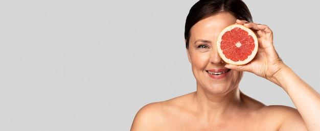 Смайлик женщина, держащая половину грейпфрута над лицом с копией пространства Бесплатные Фотографии