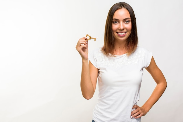 Smiley woman holding a key with copyspace Free Photo