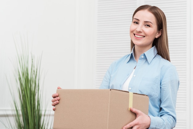 Smiley woman holding a package indoors Premium Photo