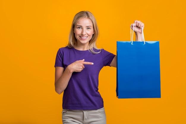 Donna di smiley che tiene e che indica al sacchetto della spesa Foto Gratuite