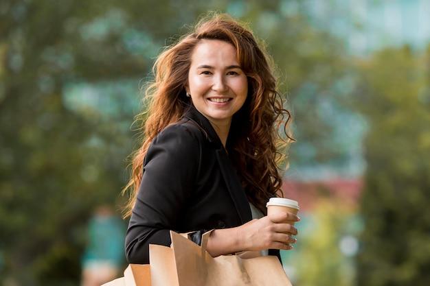 Donna sorridente che tiene i sacchetti della spesa Foto Gratuite