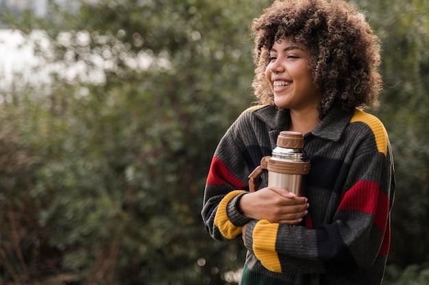 Смайлик женщина, держащая термос во время кемпинга на открытом воздухе с копией пространства Бесплатные Фотографии
