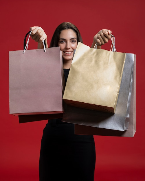 Smiley woman holding up her shopping bags Free Photo