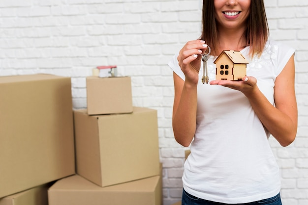 Smiley woman holding a wooden cottage and keys Free Photo