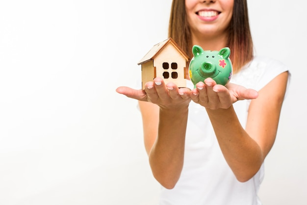 Smiley woman holding a wooden cottage and a piggy back Free Photo
