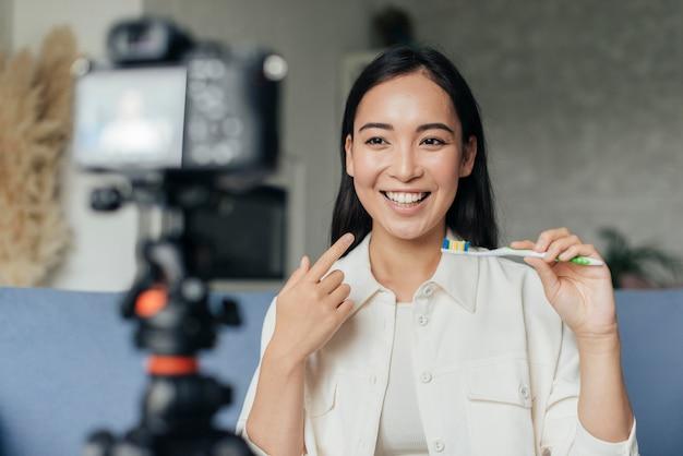 Donna sorridente in diretta streaming sui problemi dentali Foto Gratuite
