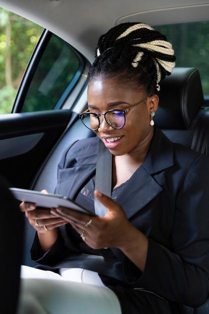 Donna sorridente guardando tablet mentre è sul sedile posteriore della sua auto Foto Gratuite