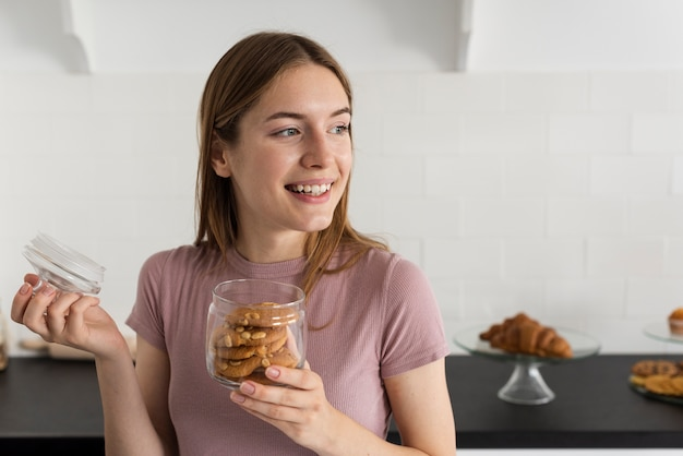 Smiley woman opening a jar with cookies Free Photo