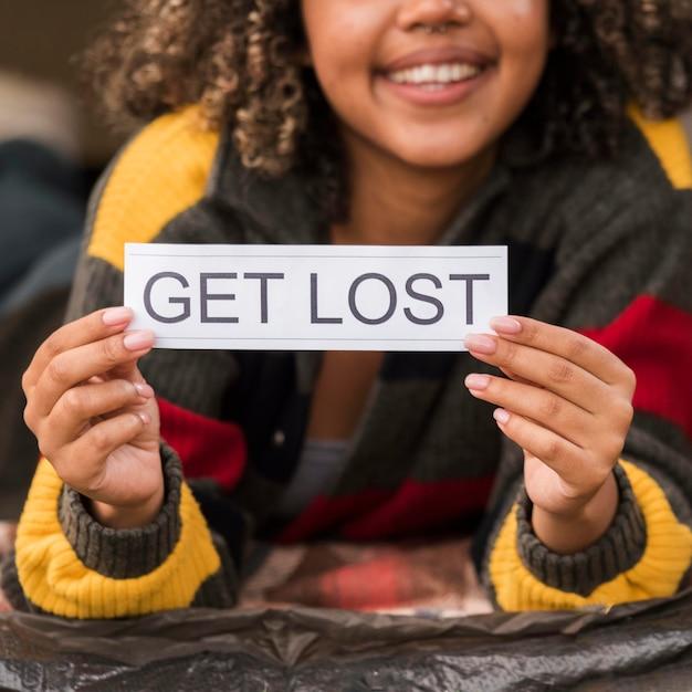 Смайлик женщина на открытом воздухе холдинг потеряться знак Бесплатные Фотографии