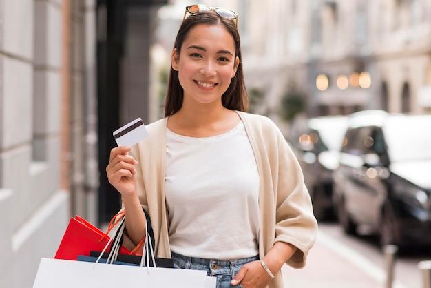 Donna sorridente all'aperto tenendo i sacchetti della spesa e la carta di credito Foto Gratuite