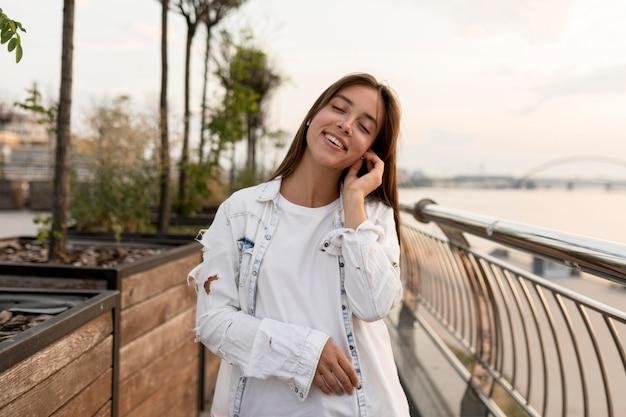 Donna sorridente all'aperto ascoltando musica su auricolari Foto Gratuite