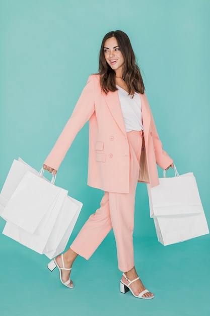 Smiley woman in pink suit with shopping nets Free Photo