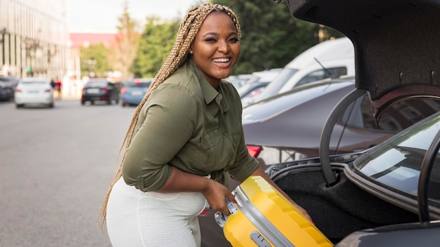 Smiley woman placing her luggage in her trunk Free Photo