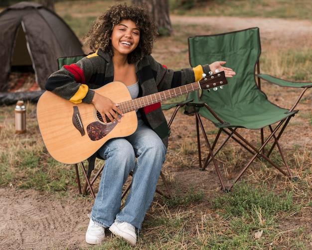 Смайлик женщина играет на гитаре во время кемпинга на открытом воздухе Бесплатные Фотографии