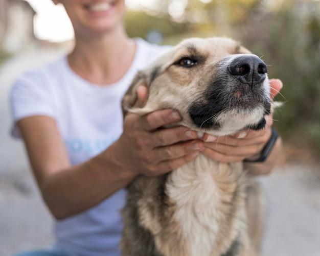 Donna di smiley che gioca con il cane sveglio all'aperto Foto Gratuite