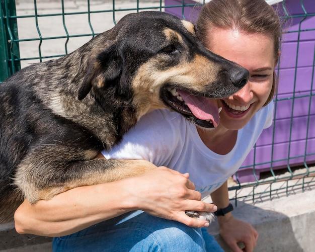 Donna sorridente che gioca con il cane in adozione Foto Gratuite