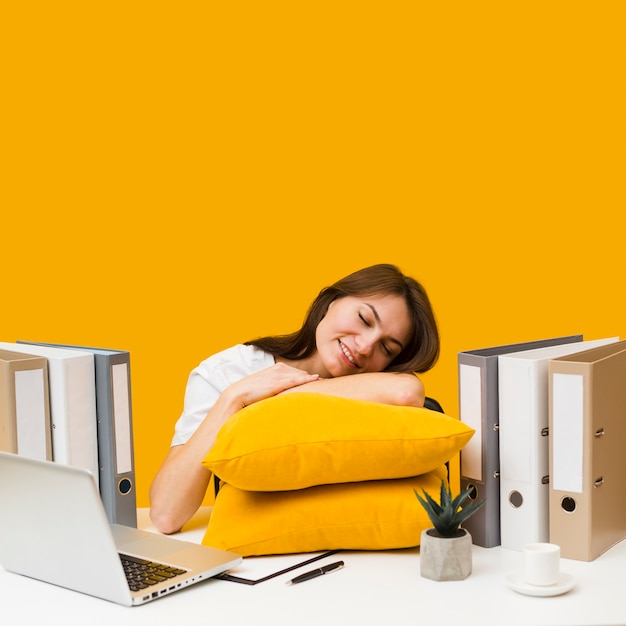 Smiley woman pleased to rest her head on pillows on top of desk Free Photo
