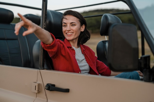 Smiley woman pointing while traveling alone by car Free Photo