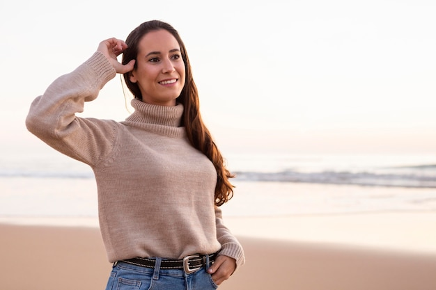 Smiley woman posing by the beach at sunset Free Photo