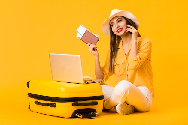 Smiley woman posing next to luggage while holding plane tickets and passport Free Photo