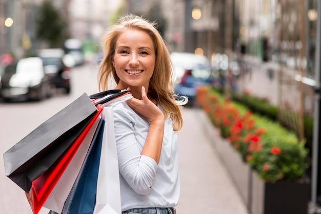 スマイリー女性が買い物袋を屋外でポーズ Premium写真