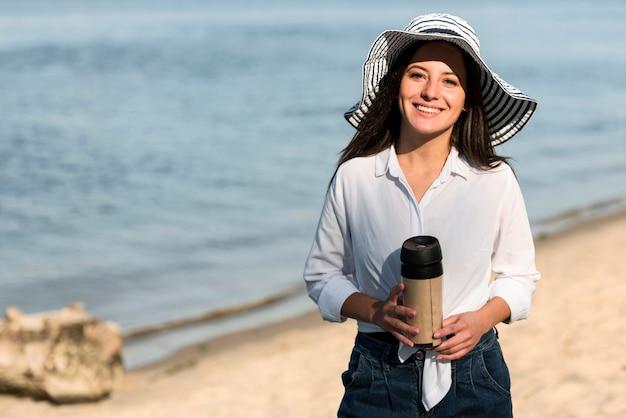 Смайлик женщина позирует с термосом на пляже Бесплатные Фотографии