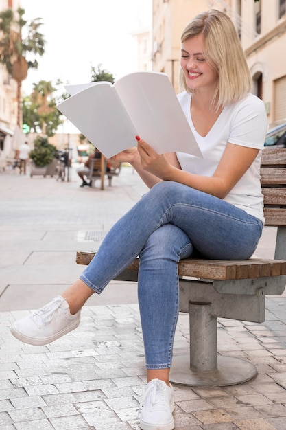 Smiley woman reading book while sitting on bench outdoors Free Photo