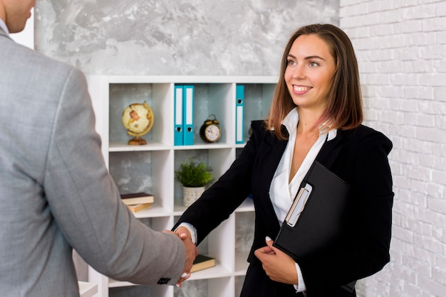 Smiley woman shakes client hand Free Photo