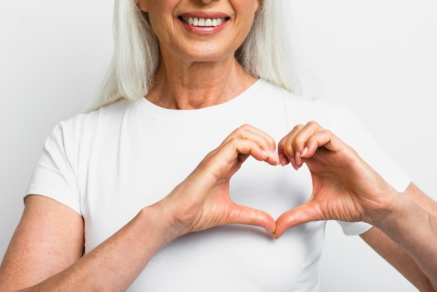 Smiley woman showing heart with hands Free Photo