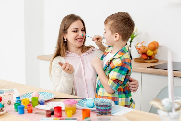 Smiley woman and son painting eggs Free Photo