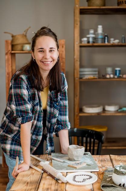 Donna sorridente in piedi nel suo laboratorio di ceramica Foto Gratuite