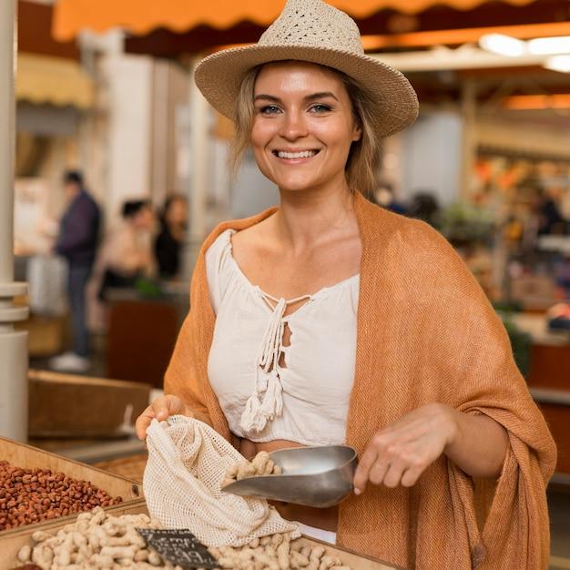 市場の場所で乾燥食品を取ってスマイリー女性 無料写真