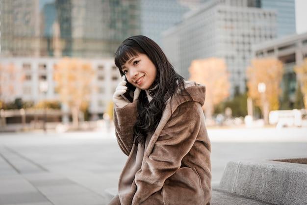 Смайлик женщина разговаривает по телефону на открытом воздухе Premium Фотографии