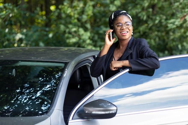 ほとんど彼女の車に乗りながら電話で話しているスマイリー女性 無料写真