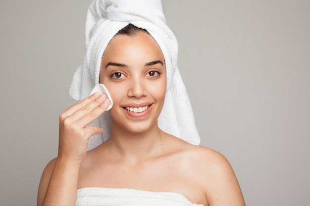 Smiley woman using a cotton pad on her face Free Photo