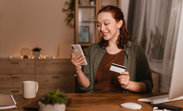 Smiley woman using her smartphone at home with credit card Free Photo