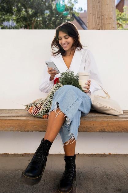 コーヒーを飲みながら屋外でスマートフォンを使用するスマイリー女性 無料写真