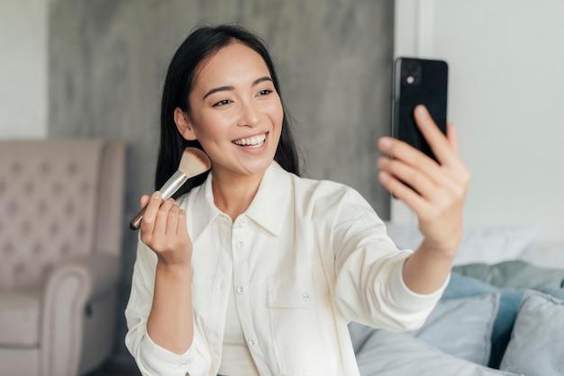 Donna sorridente che vlog con un pennello per il trucco Foto Gratuite