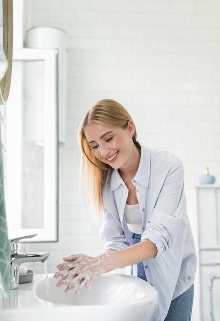 トイレで手を洗うスマイリー女性 無料写真