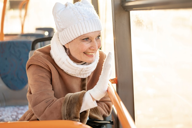Smiley woman waving from bus Free Photo