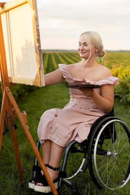Donna sorridente nella pittura su sedia a rotelle all'aperto Foto Gratuite
